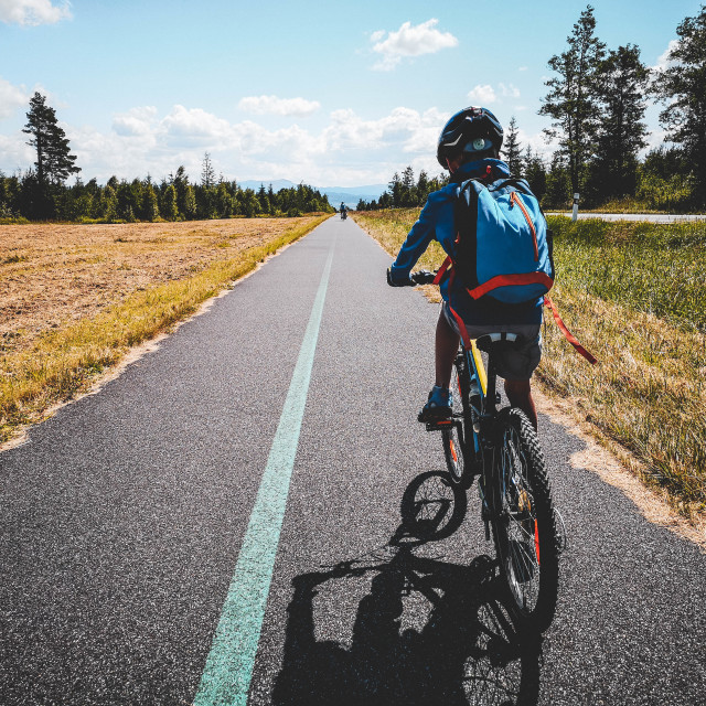 """""""Boy with a turquoise backpack riding his mountain bike on a straight asphalt cycling path"""" stock image"""