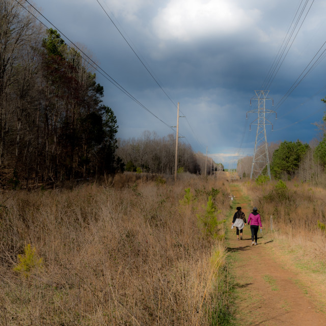 """""""Women walking along path next to power lines with storm clouds in the background"""" stock image"""