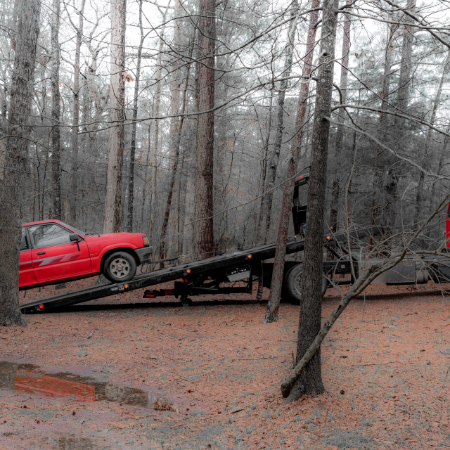 """""""Red pickup truck being loaded on red tilt bed tow truck to be hauled away"""" stock image"""