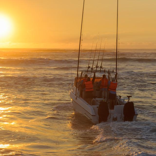 """""""Fishing boat launching at sunrise"""" stock image"""