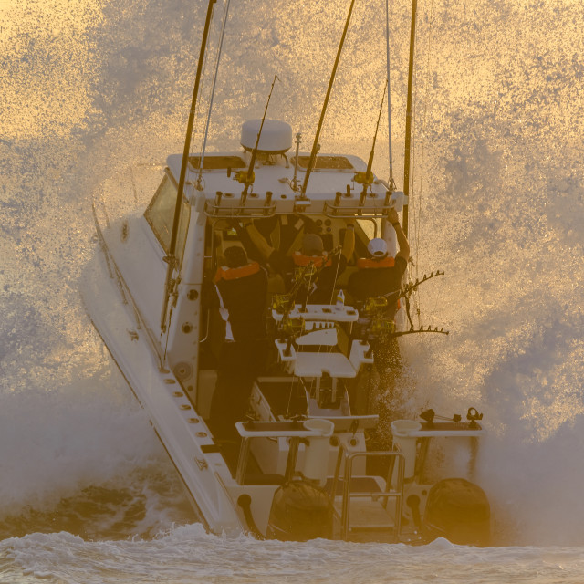 """Deep sea fishing boat punching through wave"" stock image"