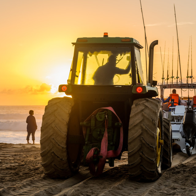 """""""Tractor pushing boat into ocean"""" stock image"""
