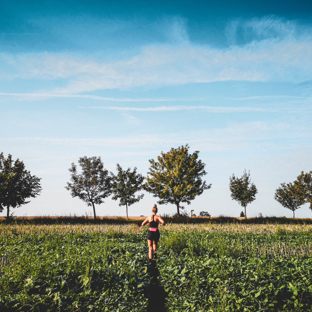"""Girl running in a field - landscape orientation"" stock image"