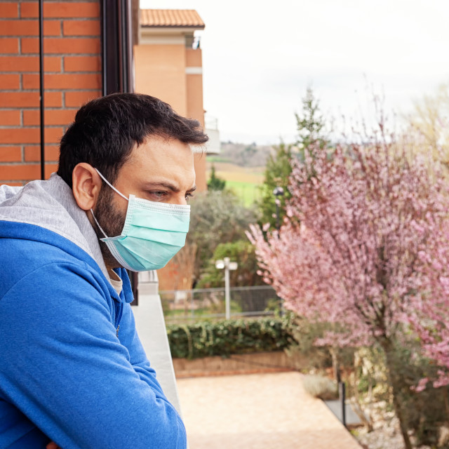 """Young caucasian man with mask looking out onto home terrace during quarantine..."" stock image"