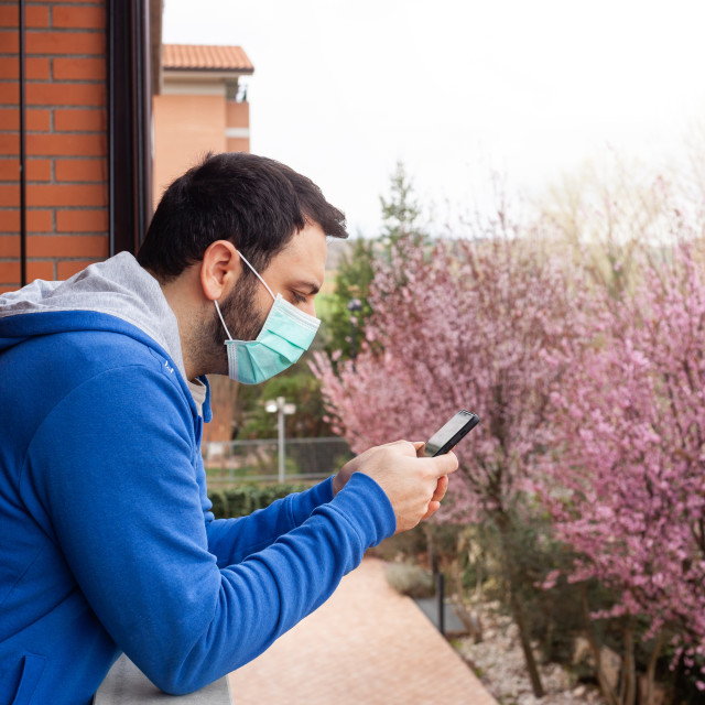 """Young caucasian man with mask looking out to home terrace using mobile phone..."" stock image"