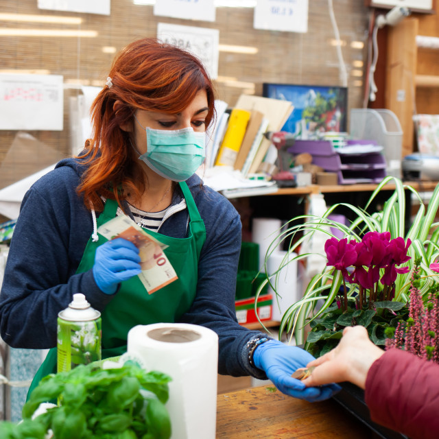 """Florist in a nursery receives a payment from a customer wearing a mask and..."" stock image"