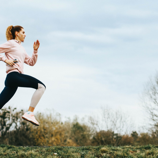 """""""Young blonde female runner running in a park with clouds in the background- stock photo"""" stock image"""