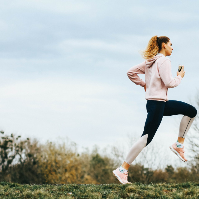 """""""Young female runner running in a park - stock photo"""" stock image"""