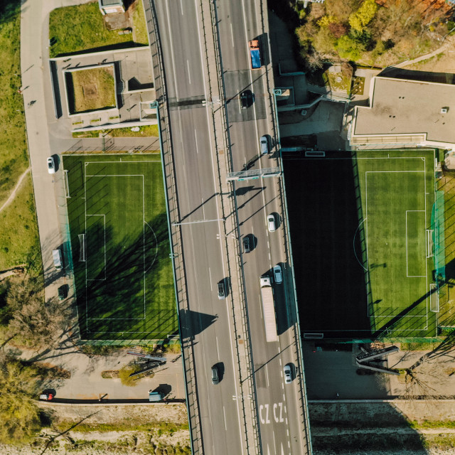 """""""Aerial view of a soccer/football and tennis field crossed by a highway bridge"""" stock image"""