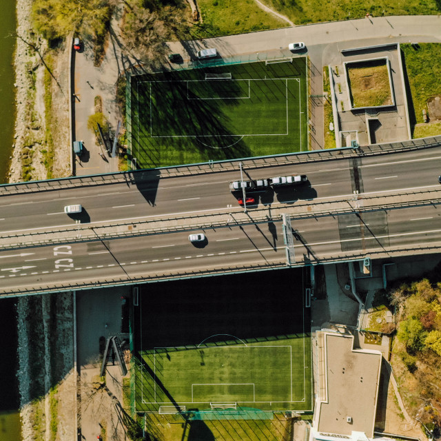 """""""Aerial view of a soccer/football field crossed by a highway with cars"""" stock image"""