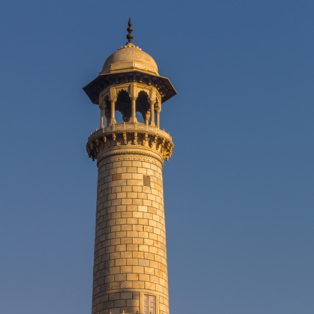 """Taj Mahal's minaret lit by the warm rays of the rising sun"" stock image"