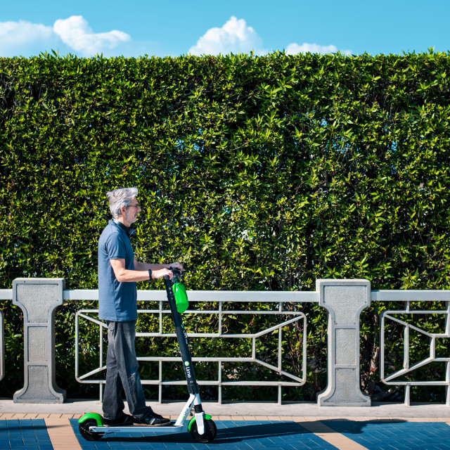 """""""Senior using electric scooter for transportation in a modern city"""" stock image"""