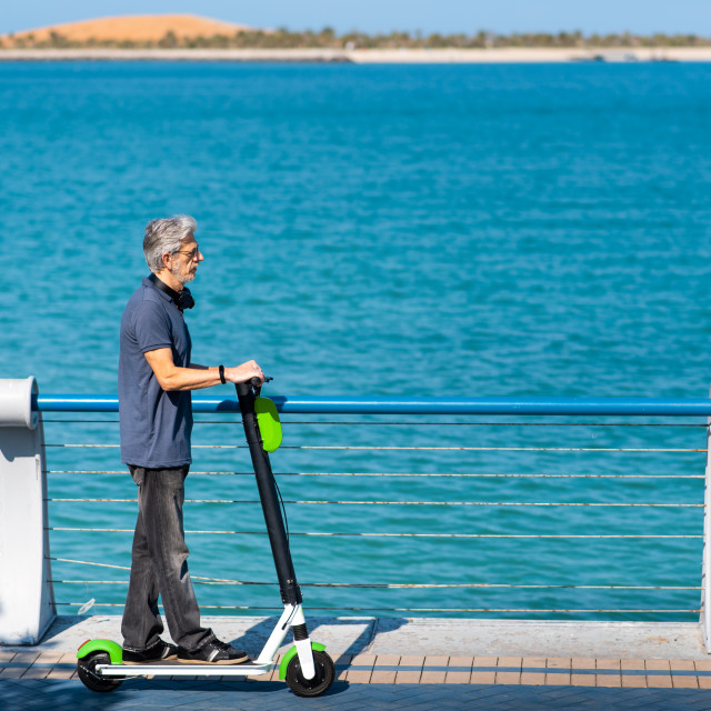 """""""Senior using electric scooter for transportation by the seaside"""" stock image"""
