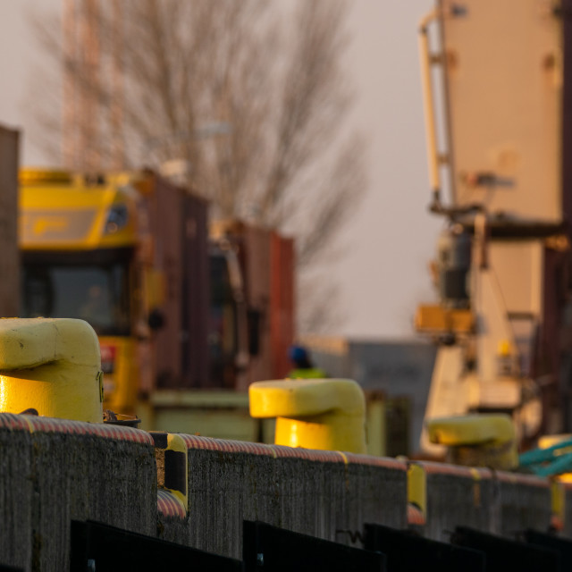 """trucks awaiting container loading on port quay, shallow depth of"" stock image"