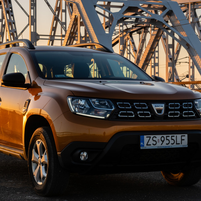 """Dacia Duster SUV standing on a steel truss bridge at sunset"" stock image"