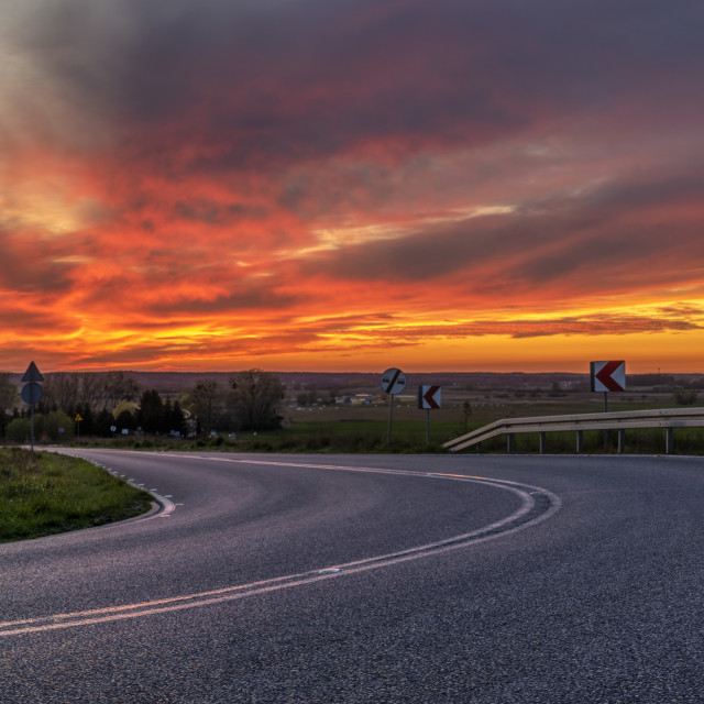 """winding asphalt road against the backdrop of a dramatic, fiery s"" stock image"