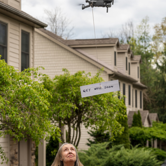 """""""Drone delivering a get well soon message to isolated senior woman"""" stock image"""
