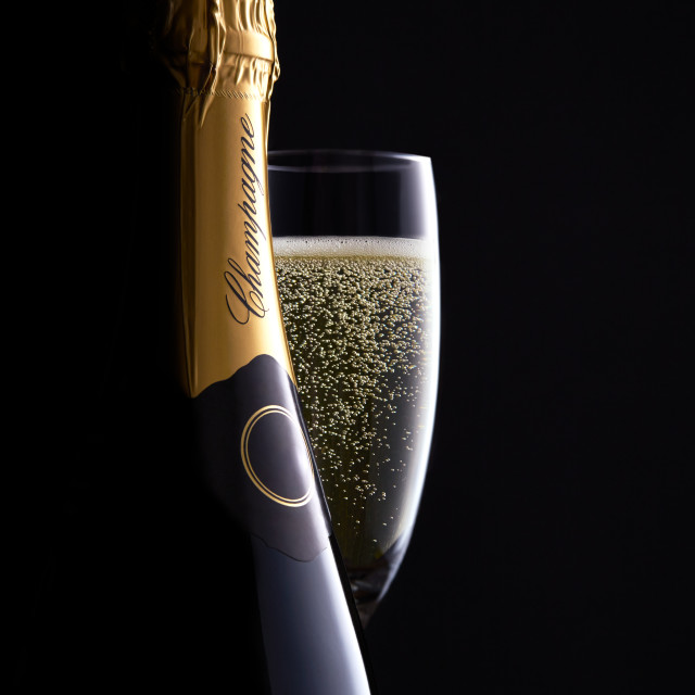 """Champagne bottle and full glass with clear bubbles moody black background, high end concept for luxury clamorous celebration, curves, silhouette, bottle shape close up."" stock image"