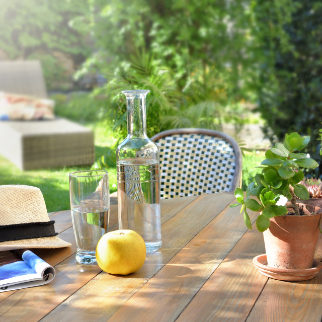 """""""close on drink glass and apple on a wooden table in garden bac"""" stock image"""