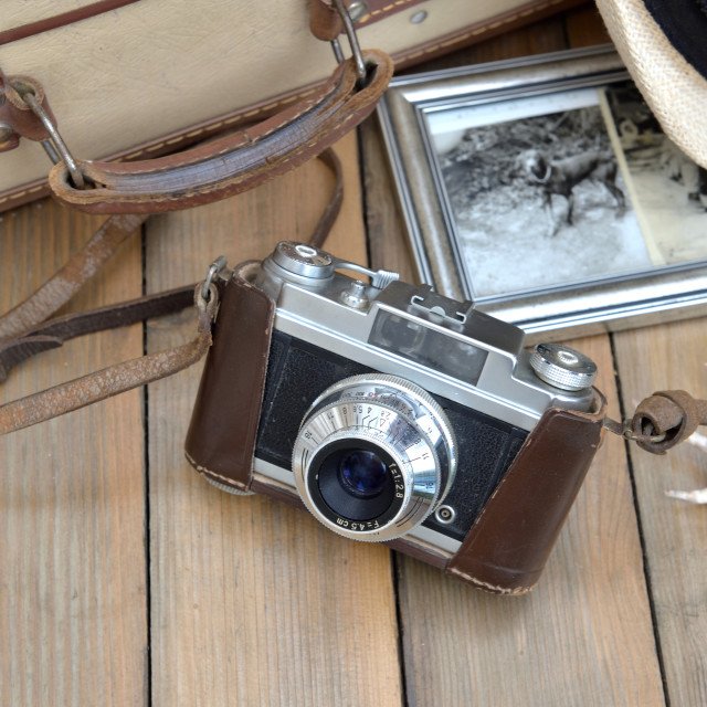 """""""retro camera with picture frame, hat suitcase and seashell on wooden table"""" stock image"""