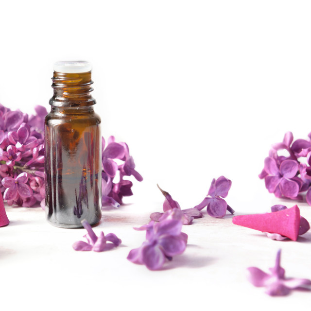 """""""oil essential bottle and incense among pink petals of lilac flowers on white background"""" stock image"""