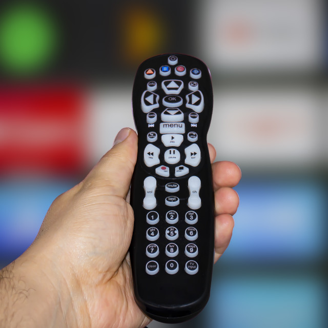 """A person holding a control remote with a television screen on the background"" stock image"