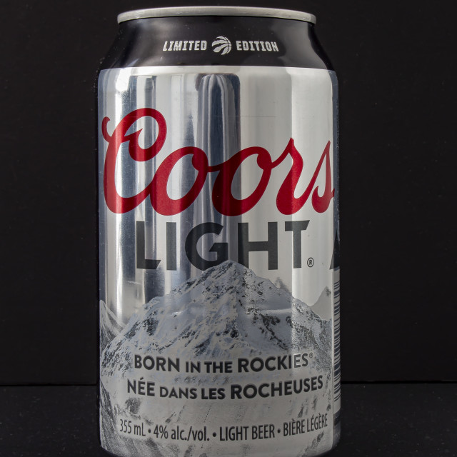 """A beer can of Coors Light special edition silver can raptors, on a black background"" stock image"
