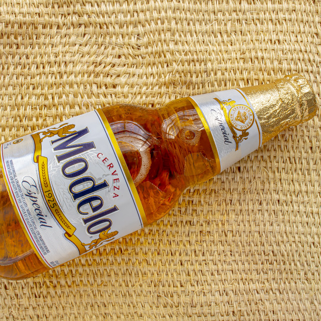 """Modelo Especial beer bottle clear bright yellow colour on a on a straw rural bag background texture"" stock image"