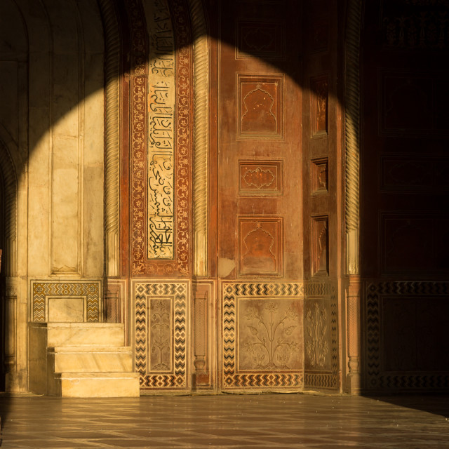 """Interior of the Taj Mahal's mosque lit by the rising sun - detailed decoration"" stock image"