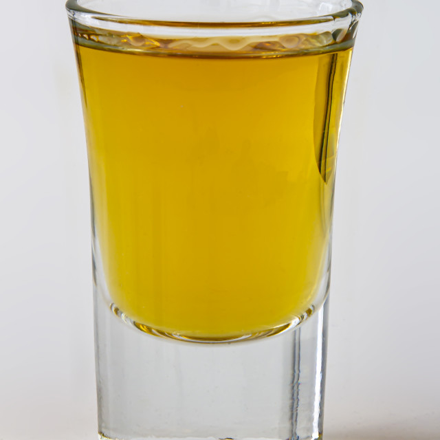 """Close up vertical view of a liquor shot drink on a white background"" stock image"