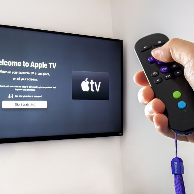 """A person holding a Roku remote control with the apple tv application open on a screen tv background"" stock image"