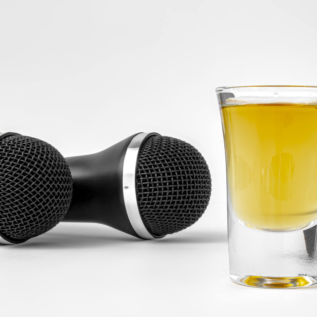 """A shoot glass with liquor and two karaoke microphones on a white background"" stock image"