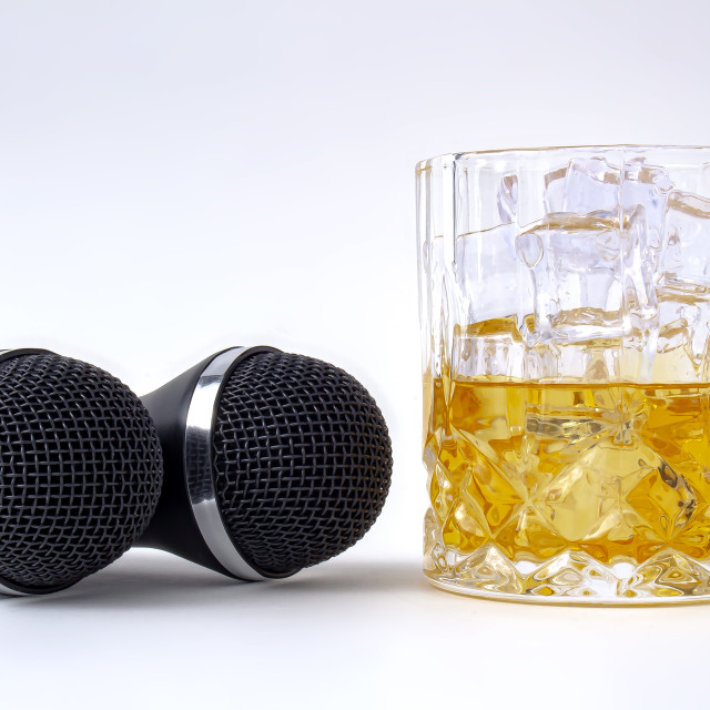 """A whisky glass with ice and liquor and two karaoke microphones on a white background"" stock image"