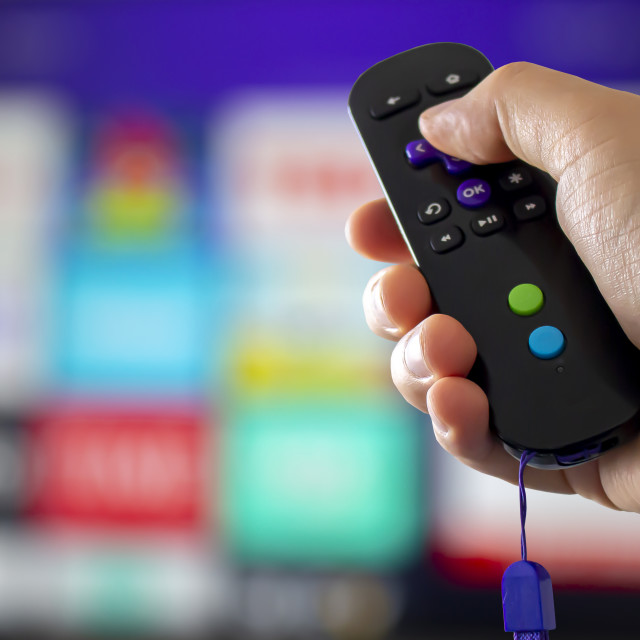 """A digital media player box control remote with a screen tv on the background"" stock image"