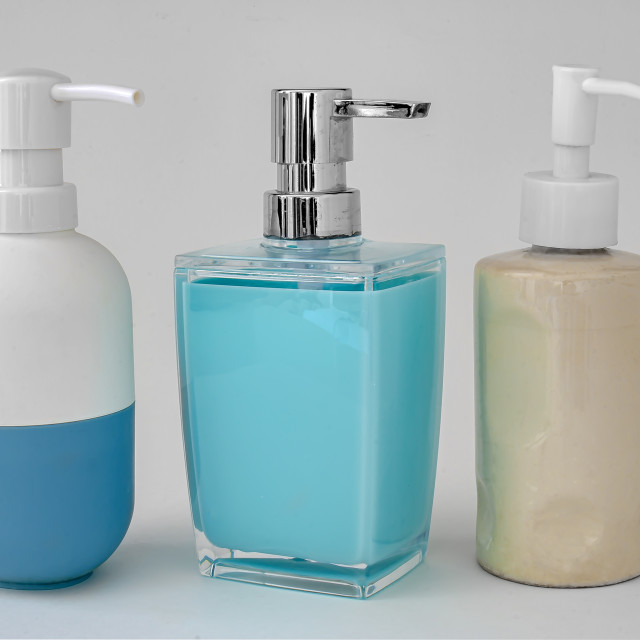 """Colorful soap dispenser for bathrooms or kitchen sinks on a grey background"" stock image"