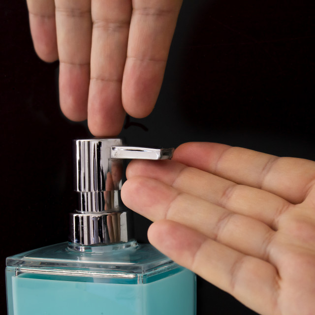 """Close up of a person getting soap from a soap dispenser on a black background"" stock image"