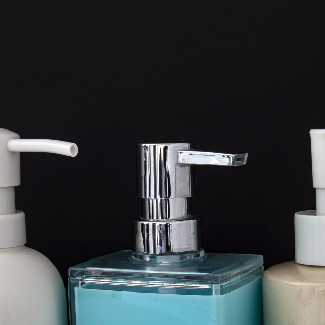 """""""Close up top view of colorful soap dispenser for bathrooms or kitchen sinks on a black background"""" stock image"""