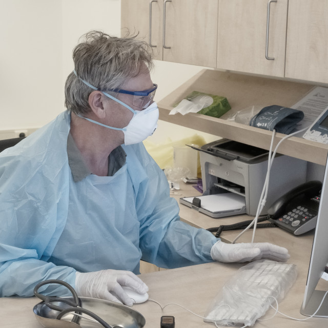 """""""Doctor during covid-19 outbreak behind computer"""" stock image"""