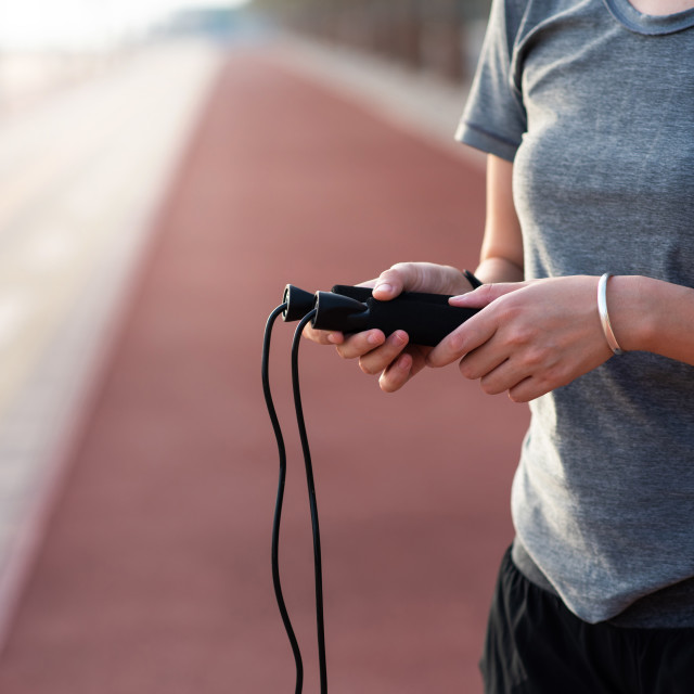 """""""Woman holding a jumping rope on a running track"""" stock image"""