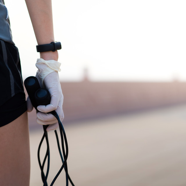 """""""Woman holding a jumping rope wearing protective surgical gloves"""" stock image"""