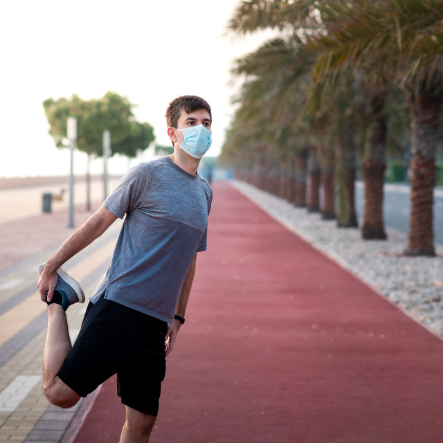 """""""Man exercising outdoors and wearing protective surgical mask"""" stock image"""