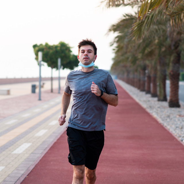 """""""Man jogging on the running track wearing protective mask"""" stock image"""