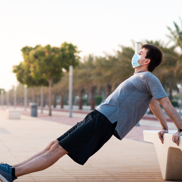 """""""Man doing triceps dips outdoors and wearing protective surgical face mask"""" stock image"""