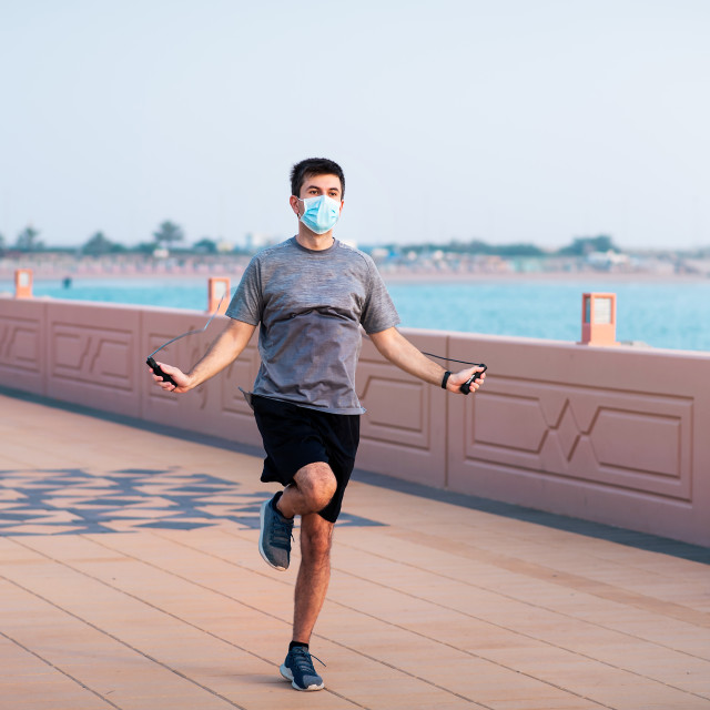 """""""Man exercising with a jumping rope and wearing protective surgical mask"""" stock image"""