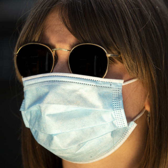 """Woman wearing a protective medical mask"" stock image"