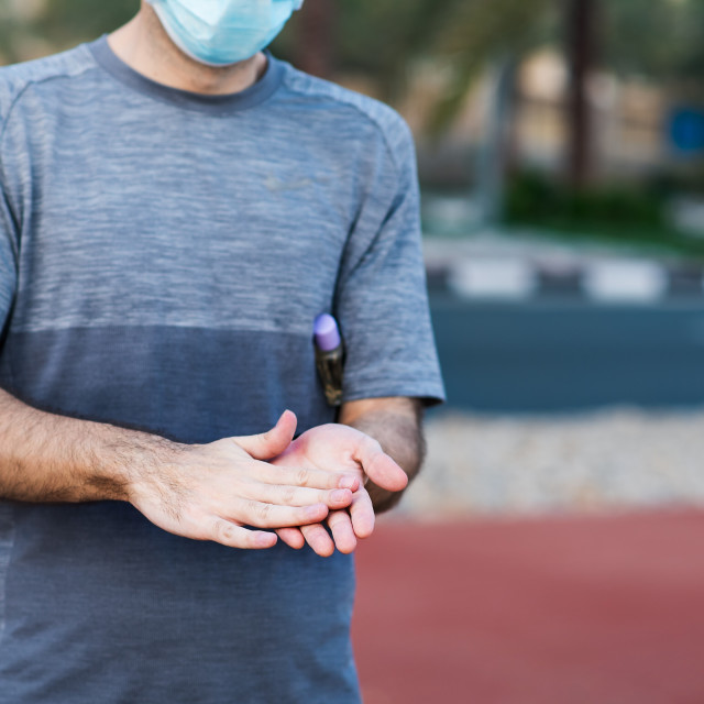 """""""Man using hand sanitizer for disinfection outdoors"""" stock image"""