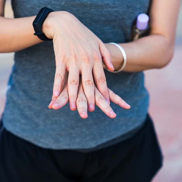 """""""Woman using hand sanitizer for disinfection outdoors"""" stock image"""
