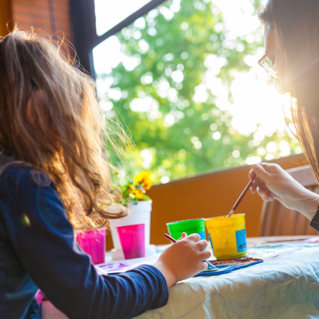 """Three year old girl coloring with her mother with watercolors."" stock image"