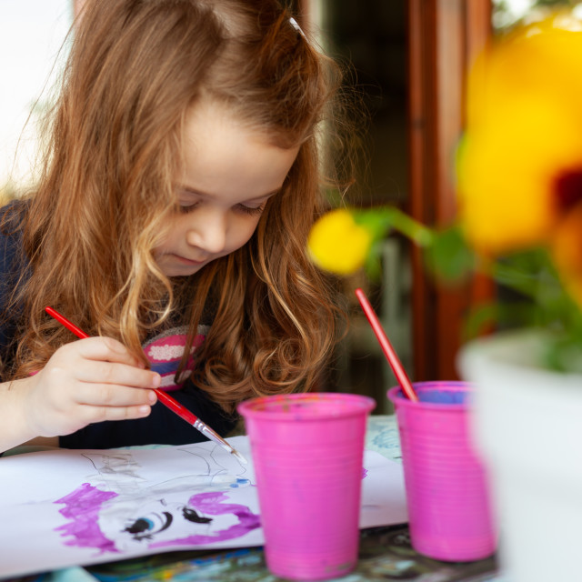 """Three year old girl paints with watercolors on the terrace."" stock image"