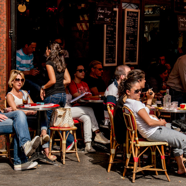"""""""Relaxing in the sun at Pavement Cafe in Paris"""" stock image"""